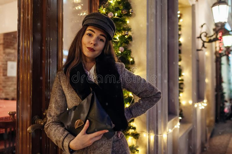 Christmas, New Year winter fashion. Woman walking on city street by decorated showcases. Stylish girl holding purse stock photo