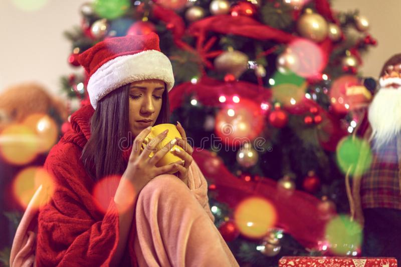 Christmas and New Year. Woman in santa`s hat is holding a cup of coffee stock image