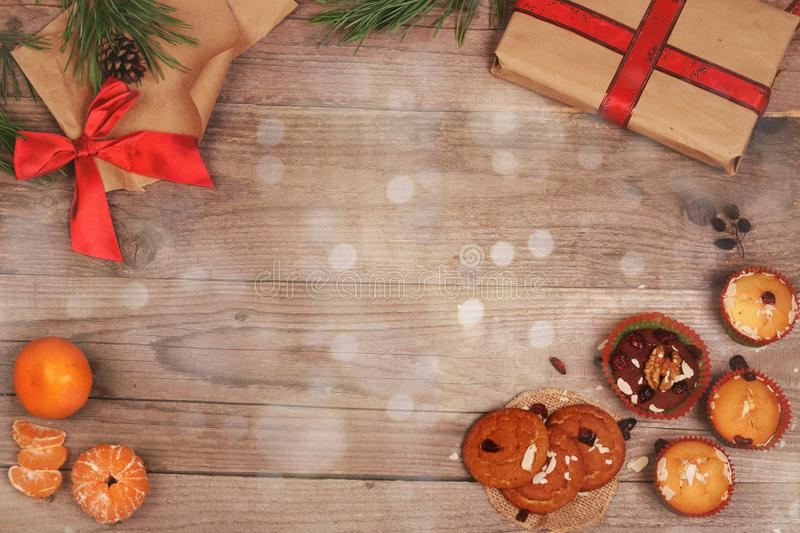 Christmas and New Year wooden background with gifts, bow, tangerines and cupcakes royalty free stock photo