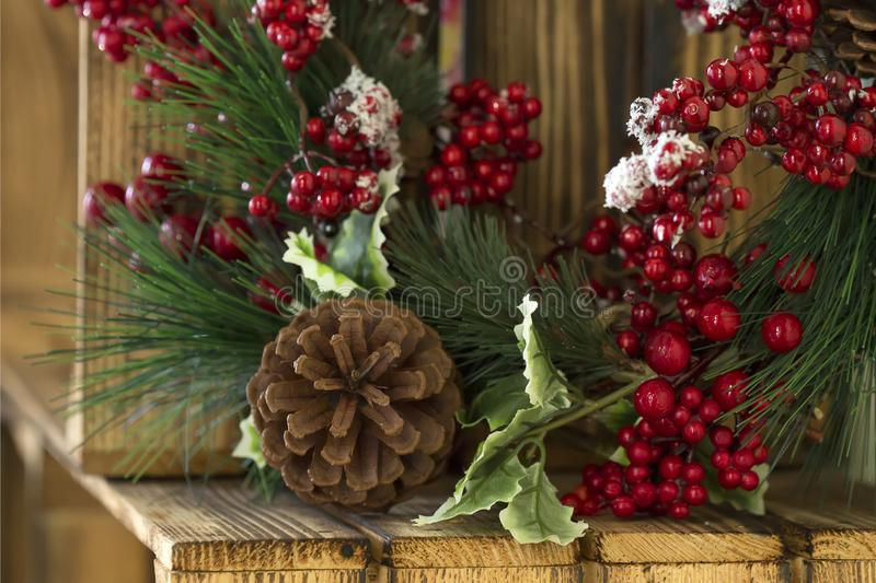New Year`s wreath on a wooden box in the village. Christmas, New Year wreath on wooden surface. Pine branches, a cone, a red ashberry and snow on wooden box royalty free stock photos