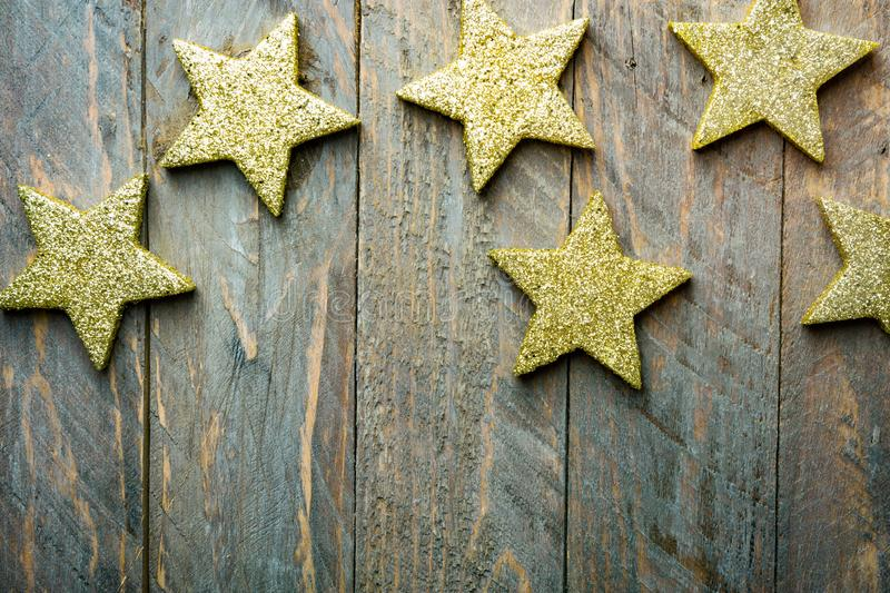 Christmas New Years background. Glittering golden stars on brown old plank wood. Vintage retro style. Creative flat lay. Poster. Greeting card template with stock image