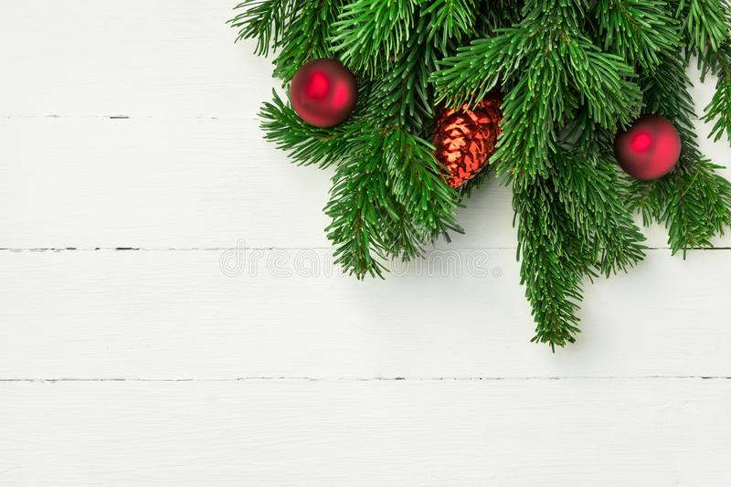 Christmas new Years background in retro vintage style with fresh fluffy fir tree branches red ornament balls on white plank wood royalty free stock image