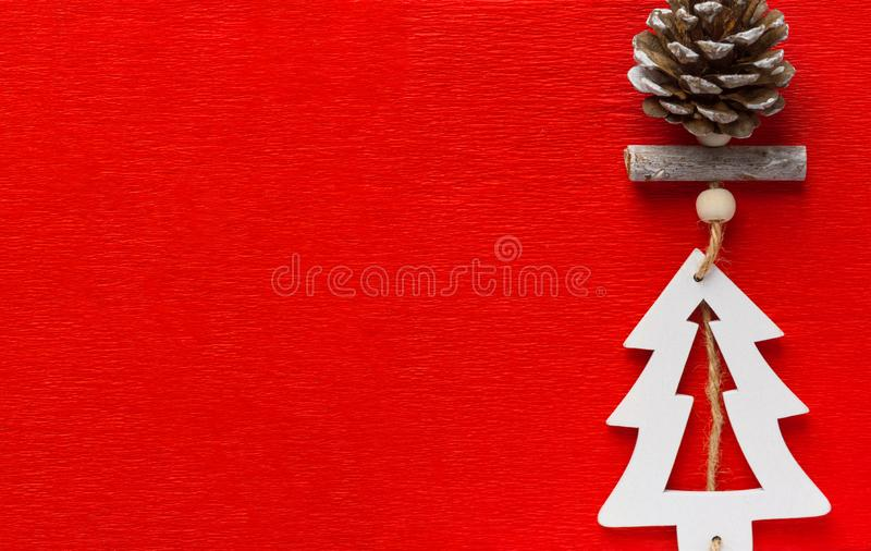 Christmas New Years decoration handmade hanger from pine cone wooden tree on twine on red velveteen background stock photo