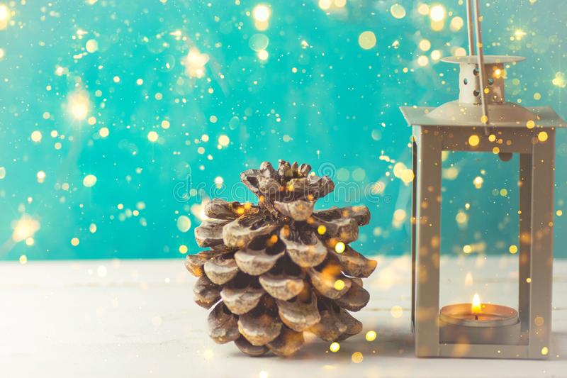 Christmas New Years greeting card with pine cone lantern with burning candle golden garland lights on turquoise background stock image