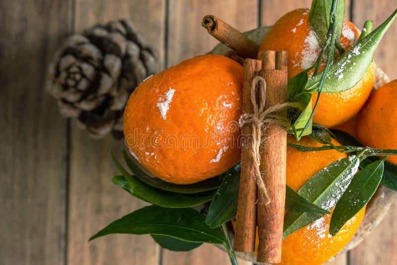 Christmas New Years greeting card poster with fresh raw tangerines on stem with green leaves cinnamon stick in box pine cone stock images
