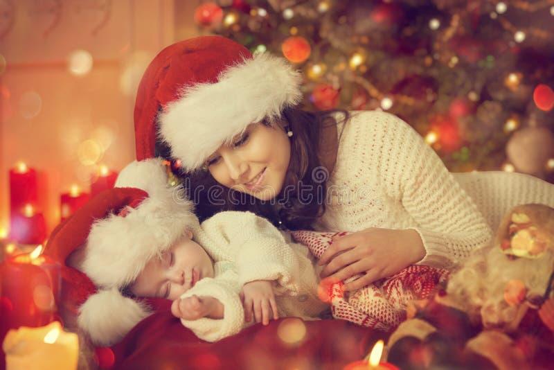 Christmas Newborn Baby and Mother, New Born Kid Sleep with Mom. In Santa Hat, Child Sleeping under Xmas Tree stock photography