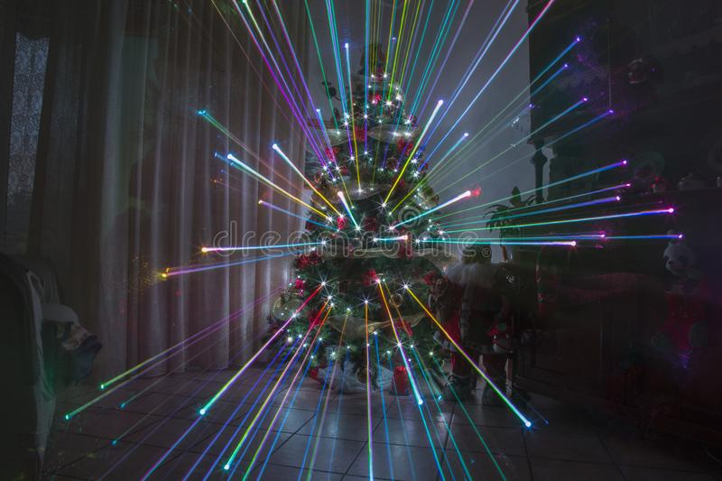 Christmas night at home with fireworks effect and rainbow lights christmas. Tree stock photos