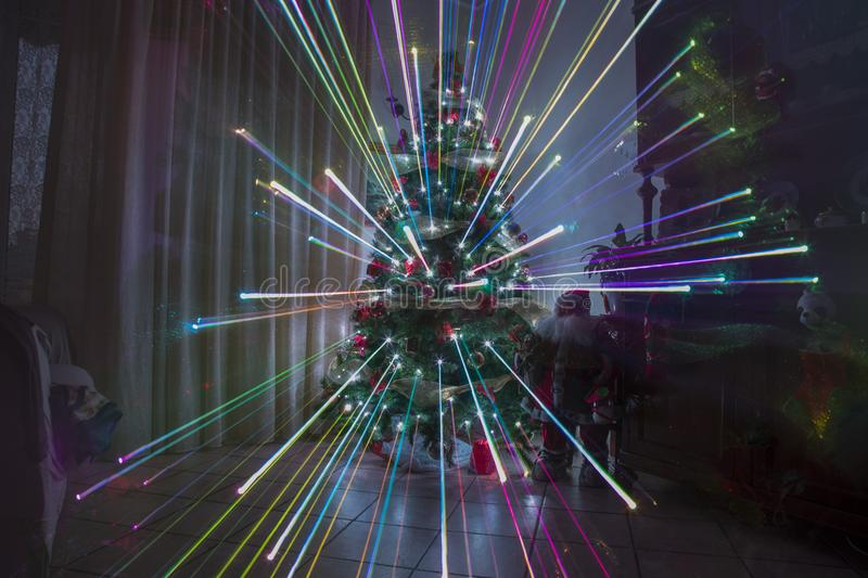 Christmas night at home with fireworks effect and rainbow lights christmas. Tree royalty free stock photography