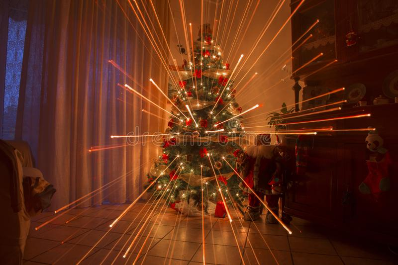 Christmas night at home with fireworks effect and warm lights. Christmas tree royalty free stock photos