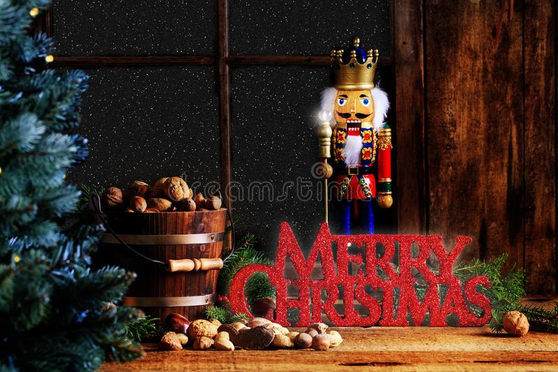 Christmas Nutcracker with Merry Christmas Greeting. A king nutcracker standing behind Merry Christmas greeting in home with rustic decor, a wooden bucket of royalty free stock images