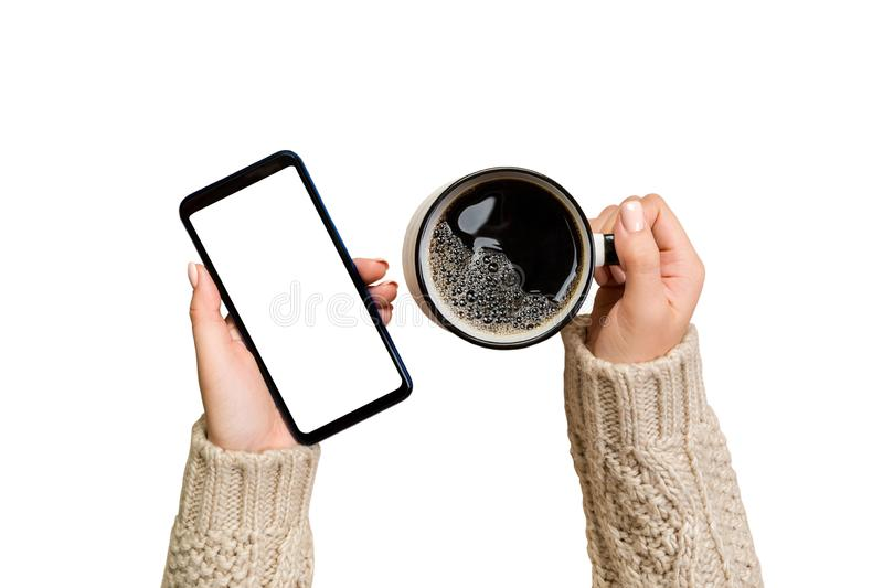 Christmas online shopping. female hands in sweater Touch screen mobile phone with cup of coffee. Woman typing on mobile phone stock images