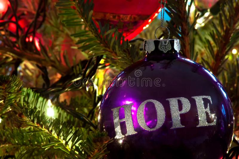 A Christmas ornament on a Christmas tree. A purple bulb Christmas ornament hanging on a Christmas tree with HOPE in silver etched on it stock images