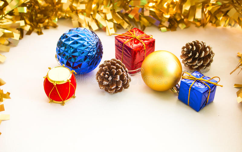 Christmas ornament composition on white background. Blue and golden fir tree balls. Red blue Christmas presents. Natural pine cone. Red Chinese drum. Design royalty free stock image
