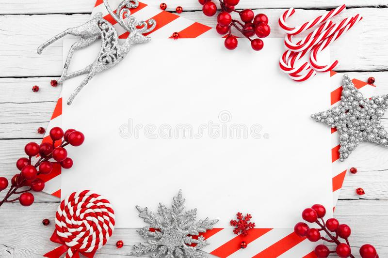 Christmas ornament made of red adornment on wooden background. Christmas ornament made of red adornment on white wooden background royalty free stock image