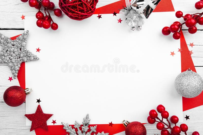 Christmas ornament made of red adornment on wooden background. Christmas ornament made of red adornment on white wooden background stock photo