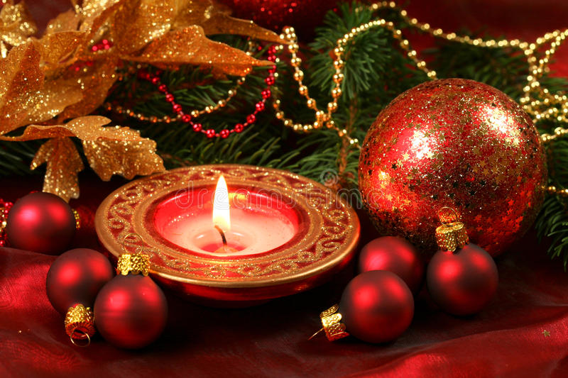 Christmas ornaments. Christmas red and golden ornaments and burning candle stock image