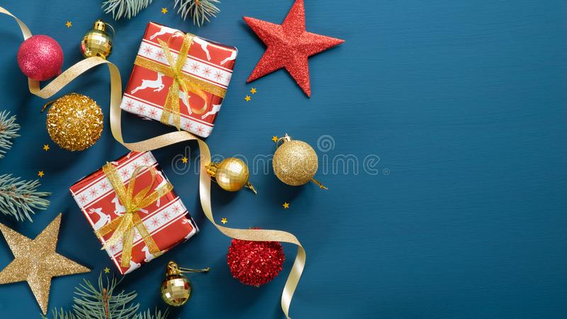 Christmas ornaments on blue background with copy space. Flat lay gift boxes, pine tree branch, golden and red balls, star, ribbon royalty free stock images