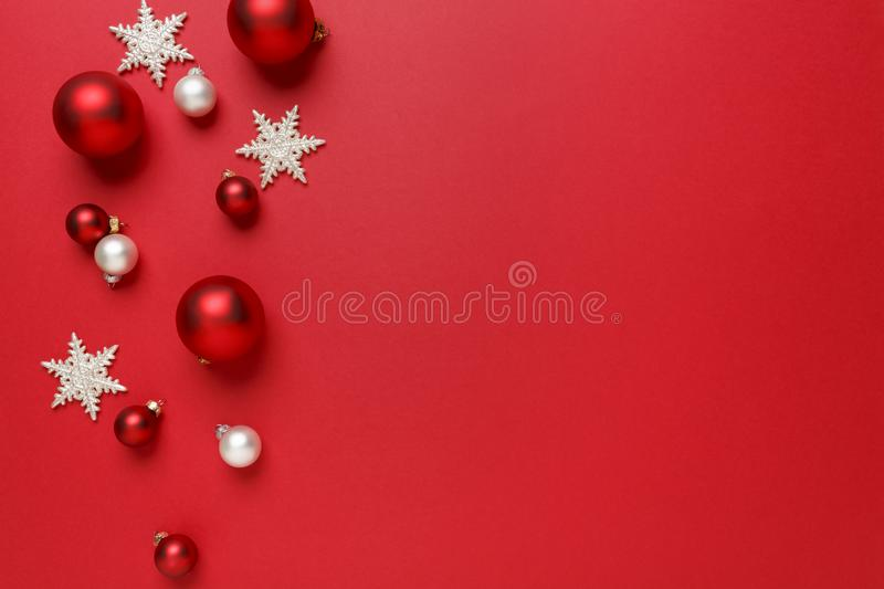 Christmas ornaments decorations background. Classic red and white glass baubles balls with giltter snowflakes horizontal border. stock photos