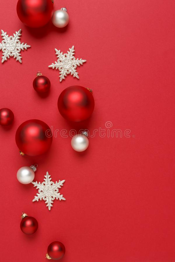Christmas ornaments decorations background. Red, silver and white glass baubles balls with glitter snowflakes vertical stock photo