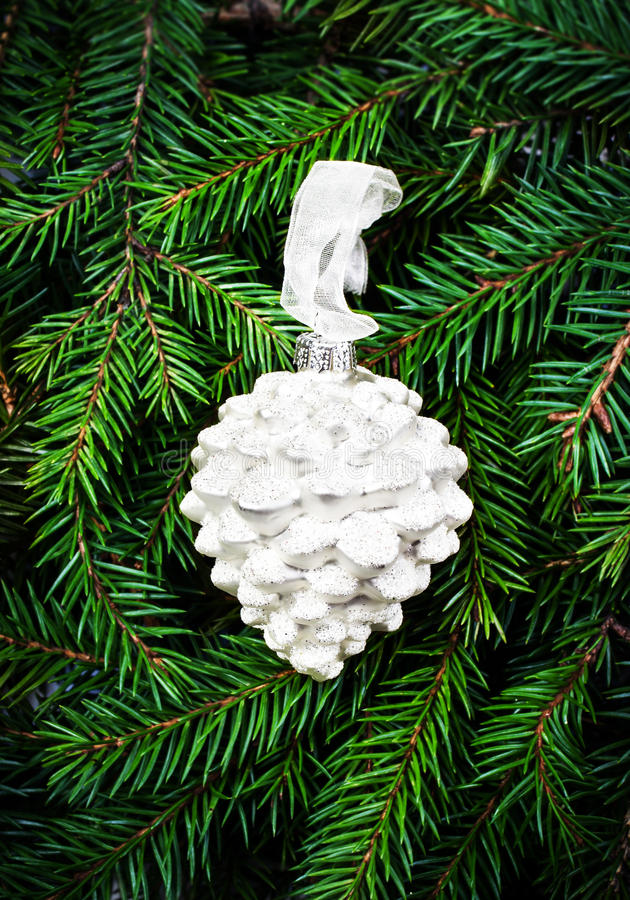 Christmas ornaments on fir tree background white for Fir cone christmas tree decorations