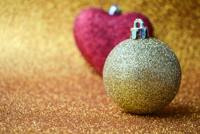 Christmas ornaments in a golden background. Red heart and gold ball in golden background stock photography