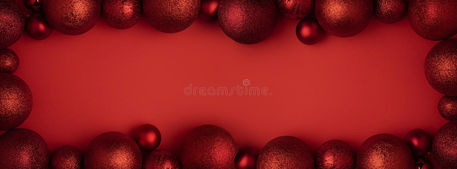 Christmas ornaments on red background. Xmas panorama of classic red glass baubles balls decorations border with copy. Space. Christmas holiday composition stock photos