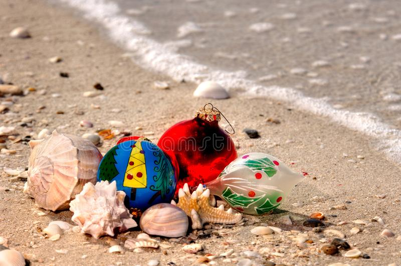 Christmas ornaments and shells on a sandy beach with a wave along the Gulf of Mexico for the holiday. stock images
