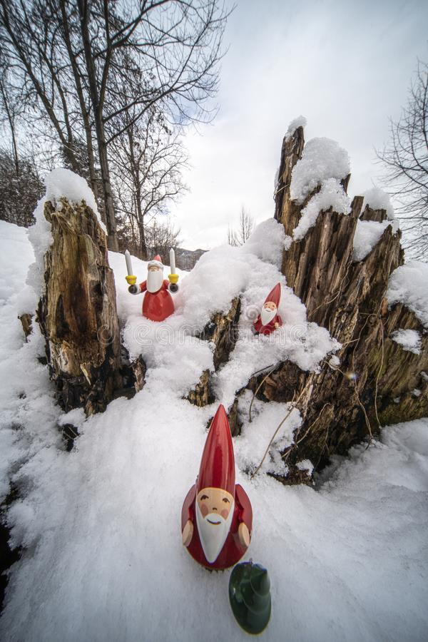 Christmas ornaments in snow. Father Christmas and his helpers outdoors in the snow with tree backdrop setting the mood for Christmas royalty free stock images