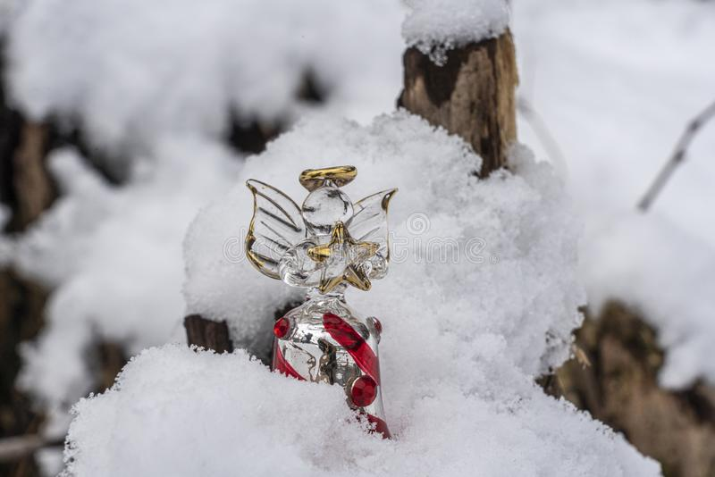 Christmas ornaments in snow. A glass angel holding a star outdoors in the snow with tree backdrop setting the mood for Christmas royalty free stock photo