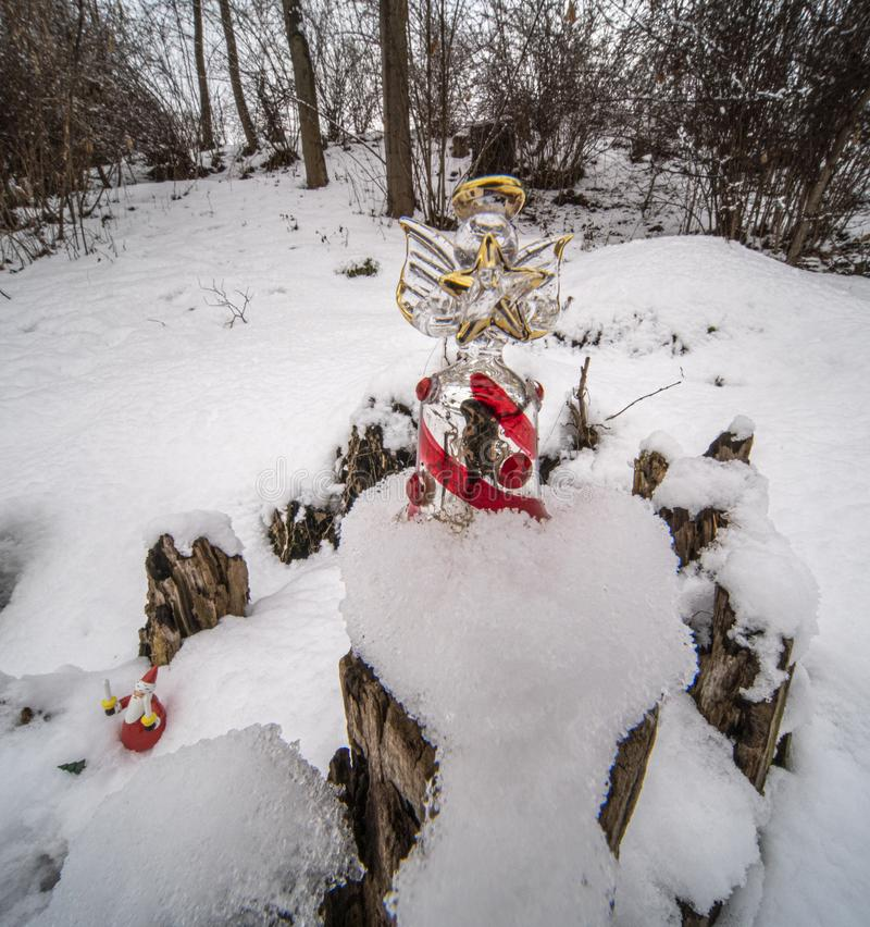 Christmas ornaments in snow. Glass angel holding a star outdoors in the snow with tree backdrop setting the mood for Christmas royalty free stock image