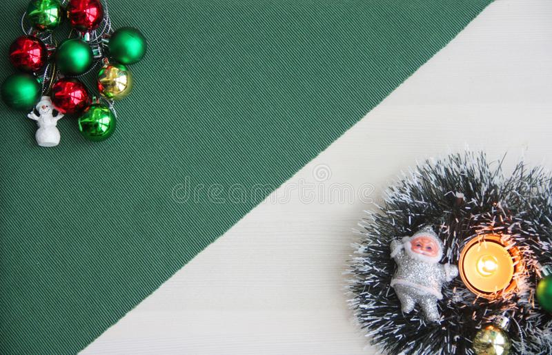 Christmas ornaments, snowman, Santa Claus, New Year`s tinsel, burning candle on a green background. stock image