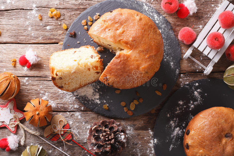 Christmas panettone bread with dried fruit and festive decoration close-up. horizontal top view stock image