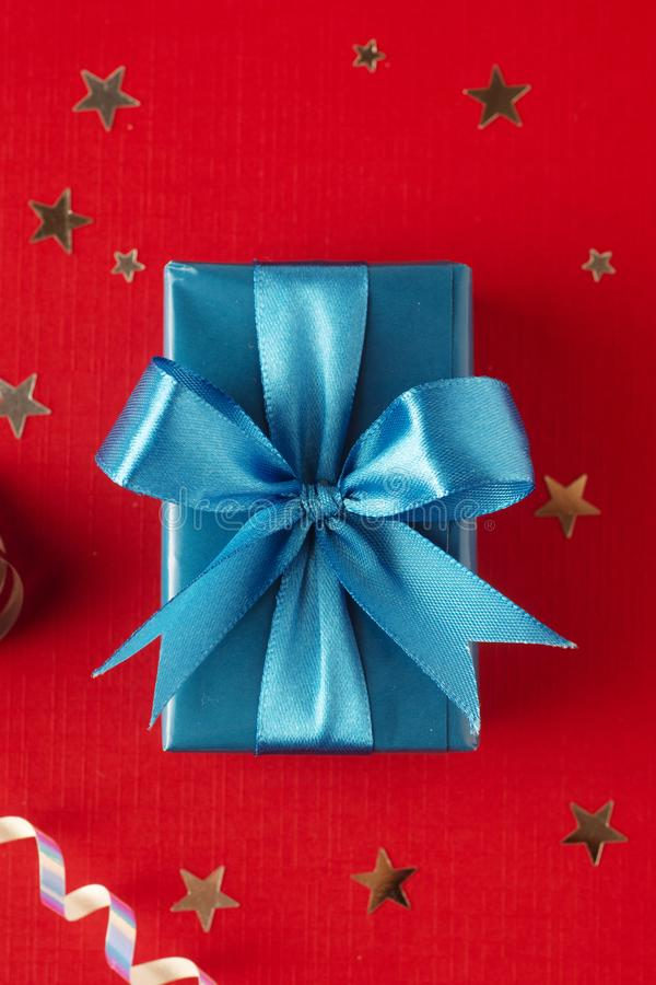 Christmas, party or birthday blue gift box or present with blue bow ribbon on red background. Christmas, party or birthday blue gift box or present with blue bow stock photography