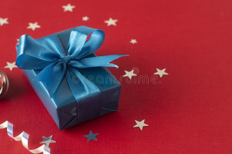 Christmas, party or birthday blue gift box or present with blue bow ribbon on red background. Christmas, party or birthday blue gift box or present with blue bow stock image