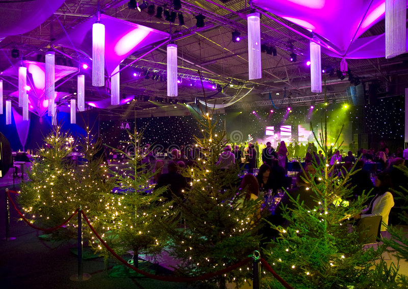 Christmas party at night. Details of Christmas party at night under bright purple lights, trees in foreground