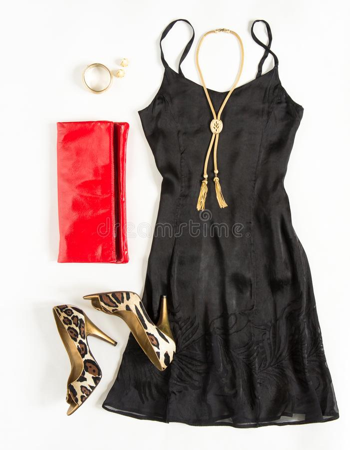 Christmas party outfit. Cocktail dress outfit, night out look on white background. Little black dress, red clutch, leopard shoes,. Gold necklace. Flat lay, top royalty free stock photography