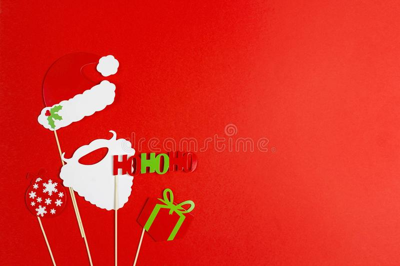 A Christmas party props for a photo booth on red background - Sa. Nta Claus hat, his beard, gift, ball, the phrase hohoho. Christmas and New year decorations royalty free stock photos