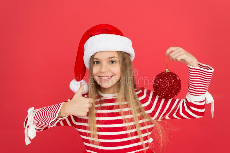 Christmas party. Winter holidays. Playful mood. Christmas celebration ideas. Shine and glitter. Child Santa Claus. Costume hat. Happy smiling face. Beautiful stock photography