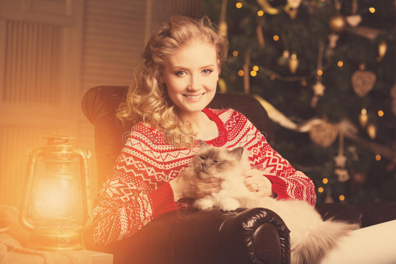Christmas party, winter holidays woman with cat. New year girl. Christmas tree in interior background stock photo
