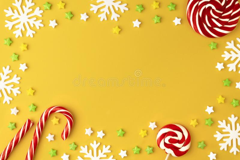 Christmas pattern with Lollipops sweets round copy space. Candy with snowflake, flat lay on yellow pastel background. royalty free stock photography
