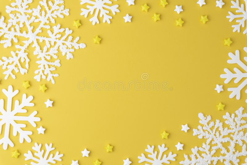 Christmas pattern with Lollipops sweets round copy space. Candy with snowflake, flat lay on yellow pastel background. royalty free stock photos