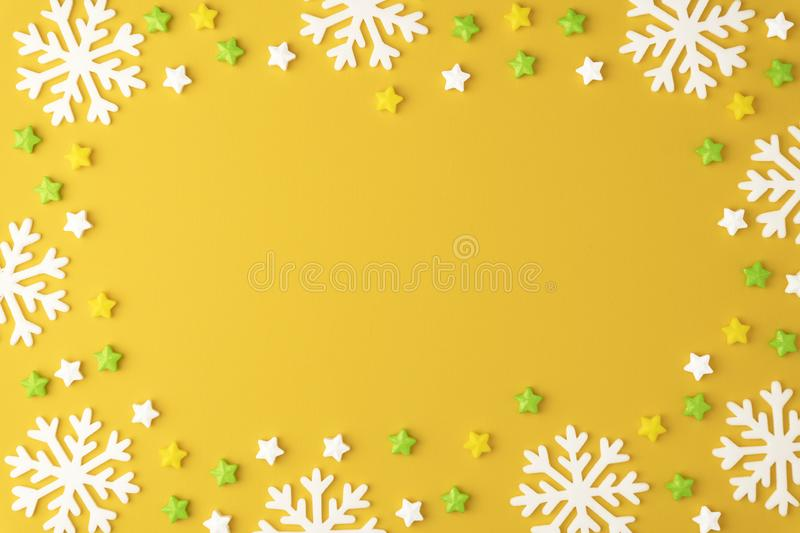 Christmas pattern with Lollipops sweets round copy space. Candy with snowflake, flat lay on yellow pastel background. stock photo
