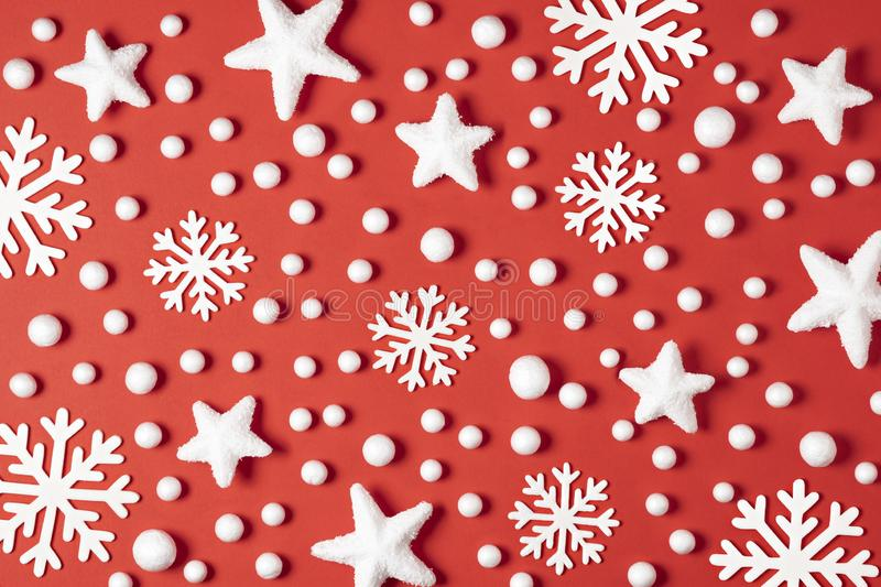 Christmas pattern made of white snowflakes, snow and stars on red background. Winter concept. Flat lay stock photos