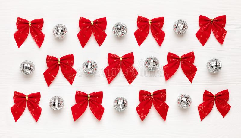 Christmas pattern of red bows and mirror balls on white wooden background royalty free stock photo