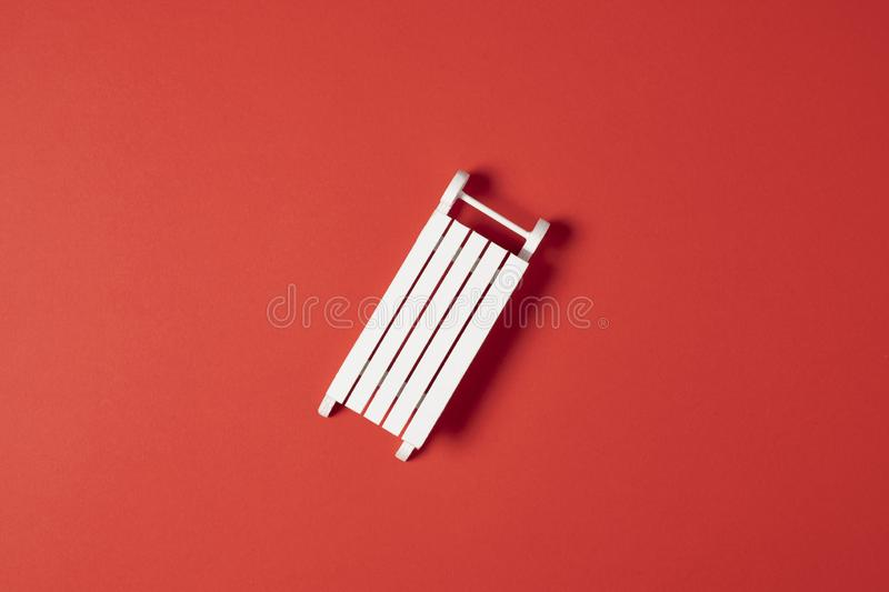 Christmas pattern white sledge on red background. Winter minimal concept. Flat lay stock photo