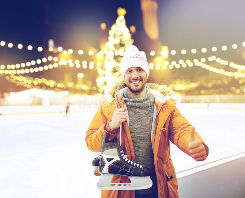 Man showing thumbs up on christmas skating rink. Christmas and people concept - happy young man with ice-skates showing thumbs up on skating rink over outdoor royalty free stock images