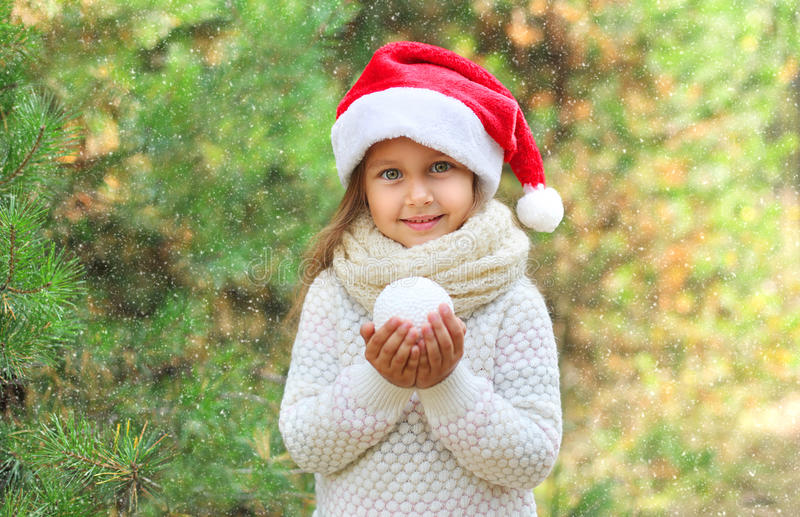 Christmas and people concept - little smiling girl child in santa hat with snowball royalty free stock photography