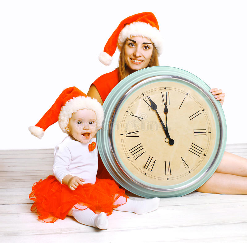 Christmas and people concept - mother with child and clock stock photo