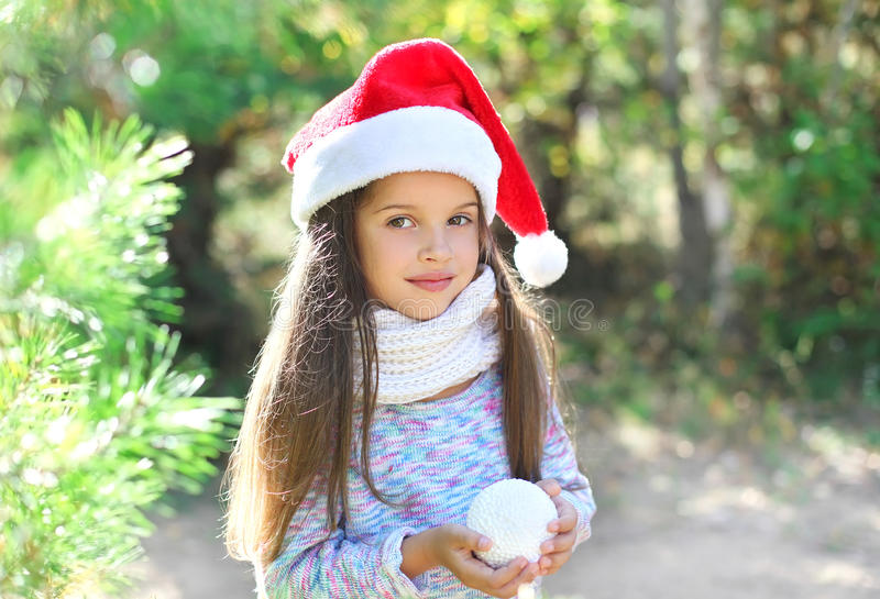 Christmas and people concept - portrait little child in santa hat with snowball royalty free stock photography