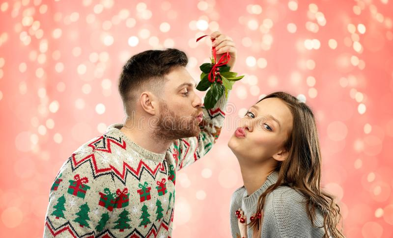 Happy couple kissing under mistletoe on christmas royalty free stock photos